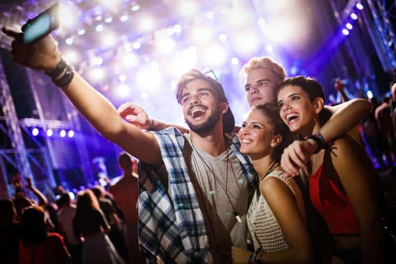Des amis heureux prennent l'auto-portraitie au festival de musique