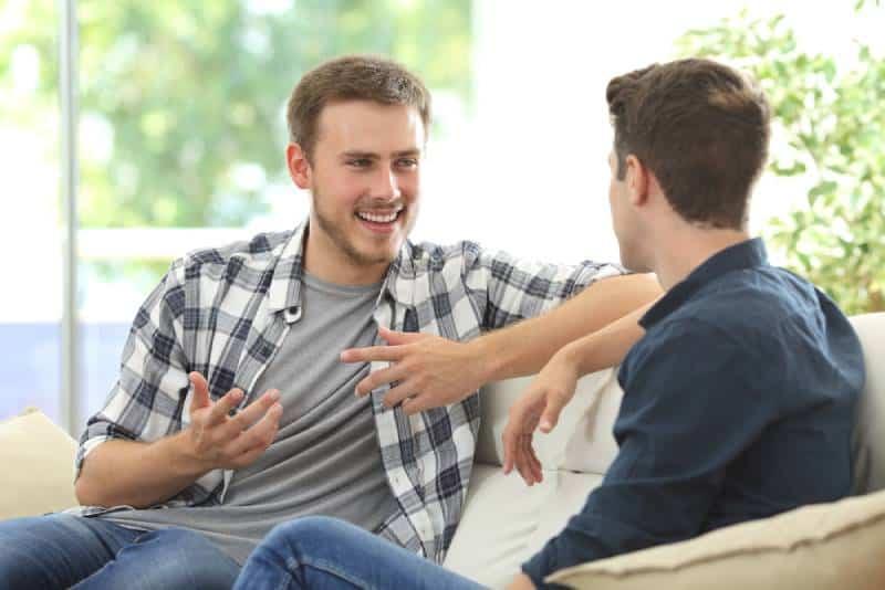 Deux amis qui discutent assis sur un canapé dans le salon