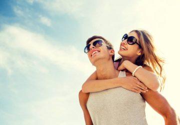 Un homme heureux qui porte sa petite amie souriante à l'extérieur