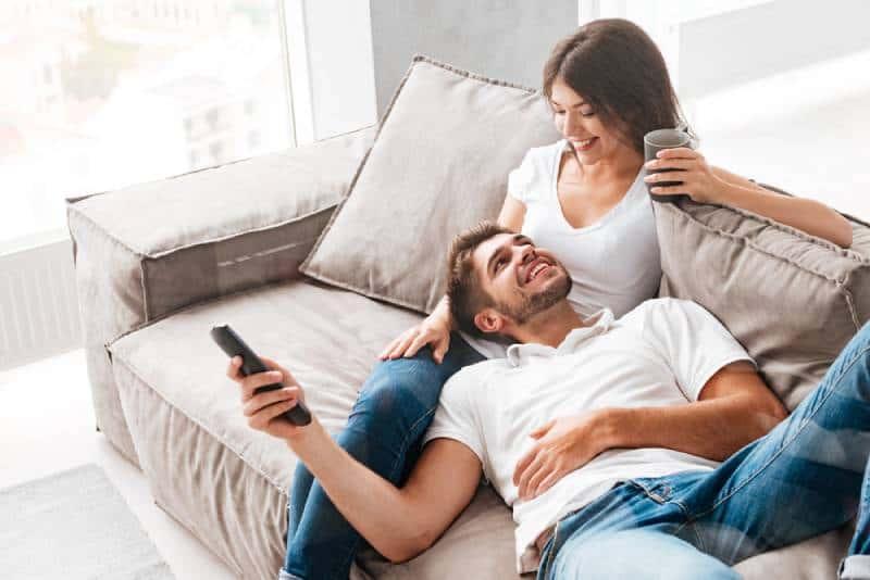 Homme se trouvant sur les jambes de petite amie dans le sofa à la maison