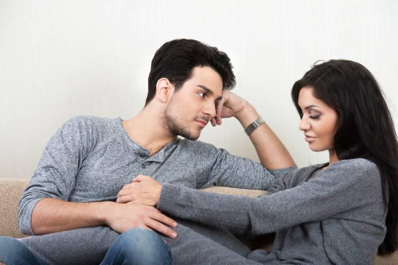 Jeune couple heureux discutant ensemble assis sur un canapé