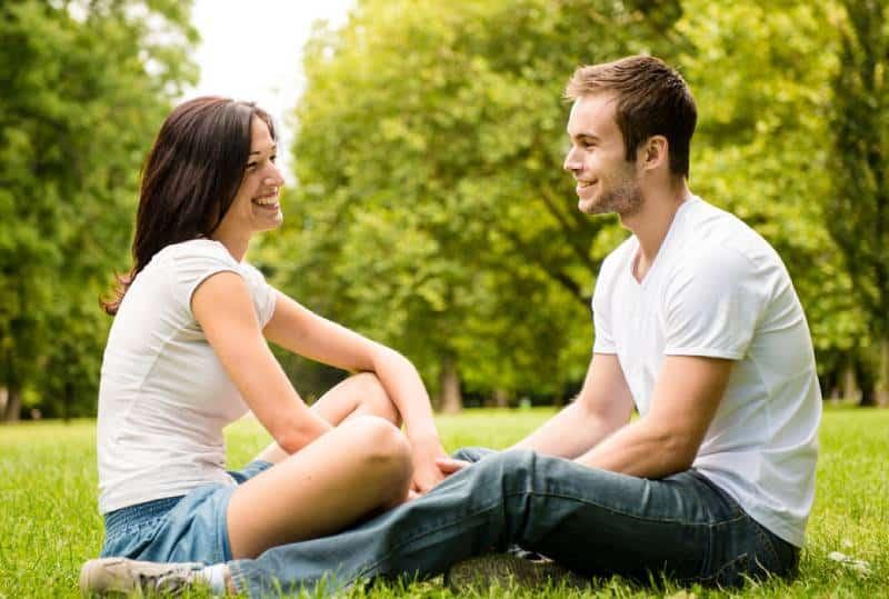 Jeune couple heureux discutant ensemble en plein air