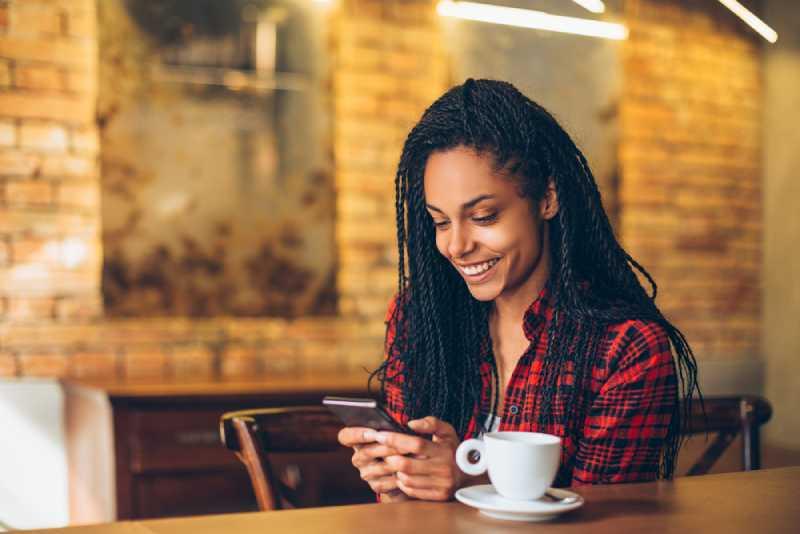 Jeune femme au café utilisant un téléphone portable
