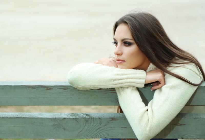 Jeune femme solitaire sur un banc dans un parc
