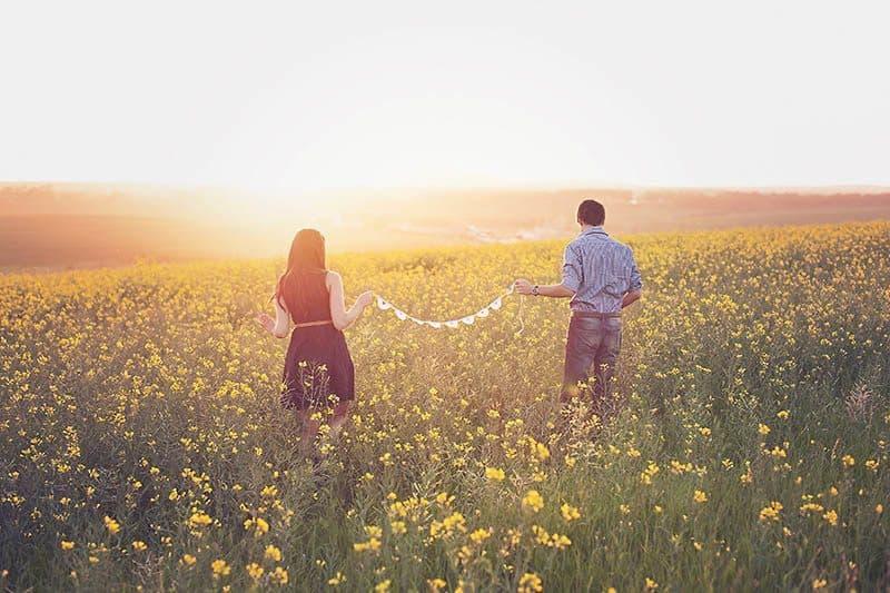 homme et femme dans un champ de fleurs