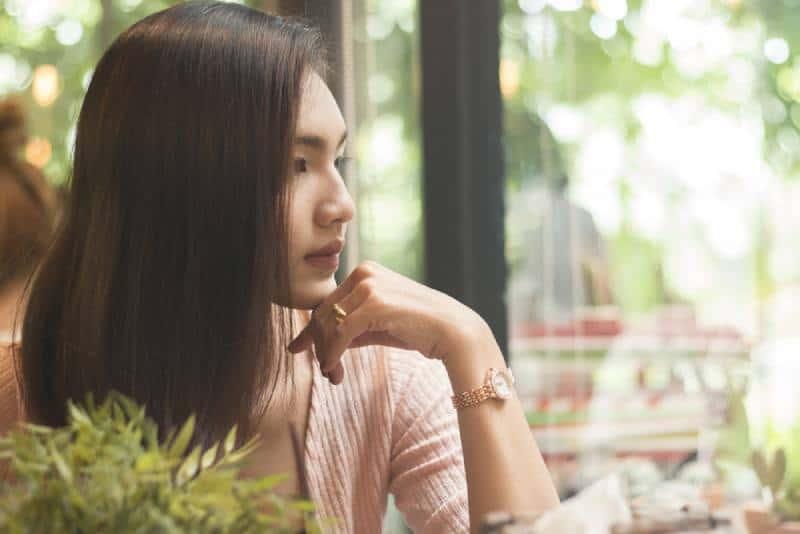 Les femmes asiatiques qui pensent ou qui manquent ont laissé un bon souvenir dans un café