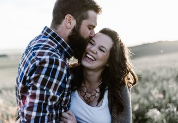 Un homme embrasse sa petite amie souriante à l'extérieur