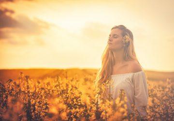 femme blonde aux yeux fermés dans le champ de fleurs
