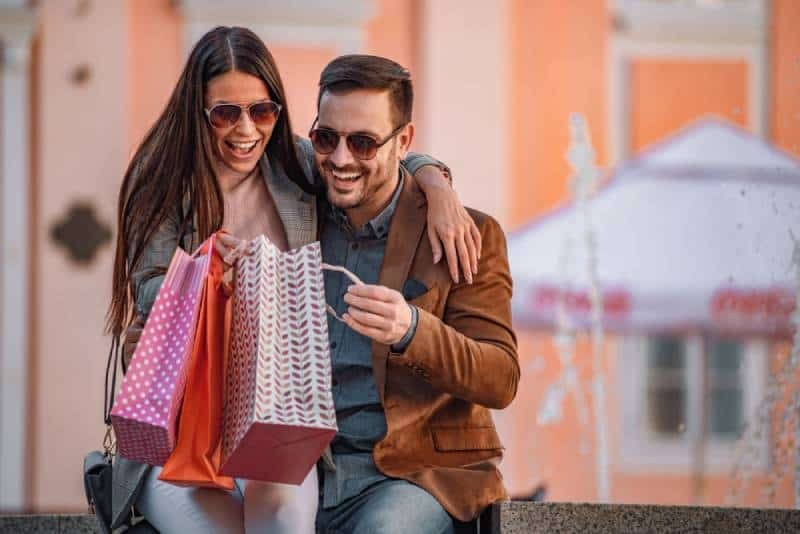 Portrait d'un couple heureux et souriant en tournée de shopping