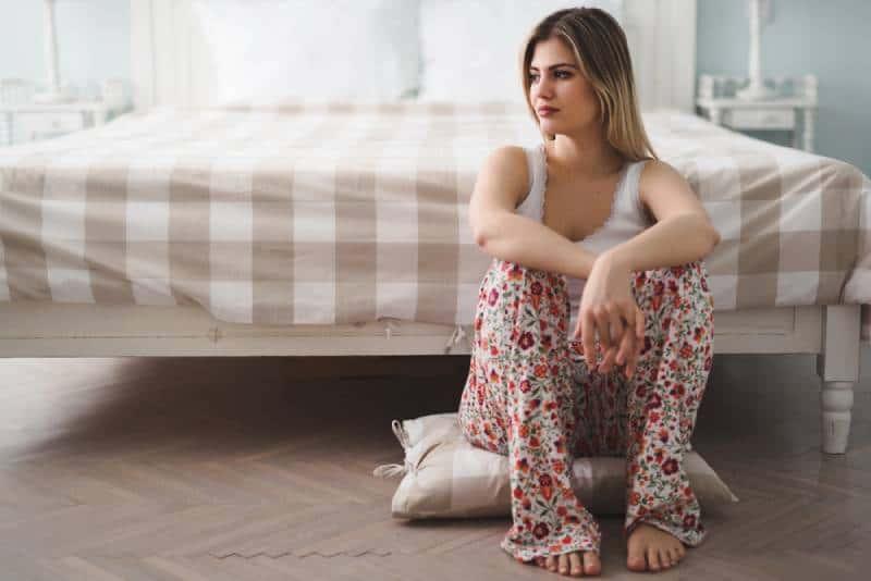fille triste s'asseyant au plancher dans la chambre à coucher