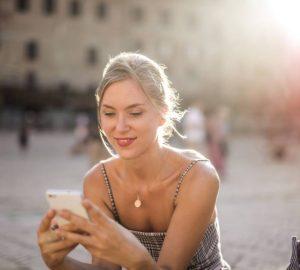 Une fille souriante envoie un SMS au téléphone à l'extérieur