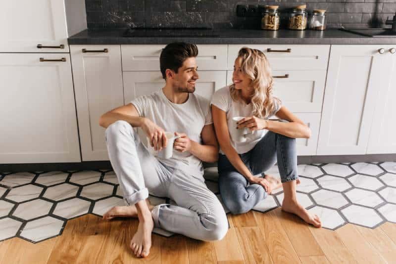 couple heureux assis par terre dans la cuisine