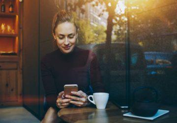 Une smiliwoman envoie des SMS au téléphone dans un café