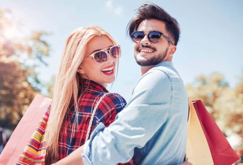 Un beau jeune couple qui aime faire du shopping, s'amuser ensemble dans la ville.