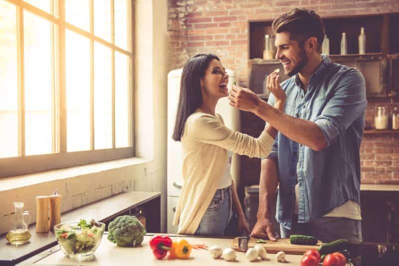 Un beau jeune couple se nourrit et sourit tout en cuisinant dans la cuisine de la maison