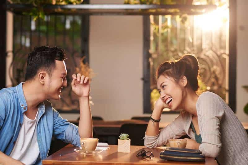 Un couple d'Asiatiques rigolant en train de sortir au café