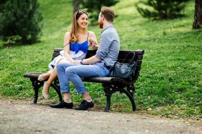 Un couple d'amoureux romantiques assis sur un banc de parc