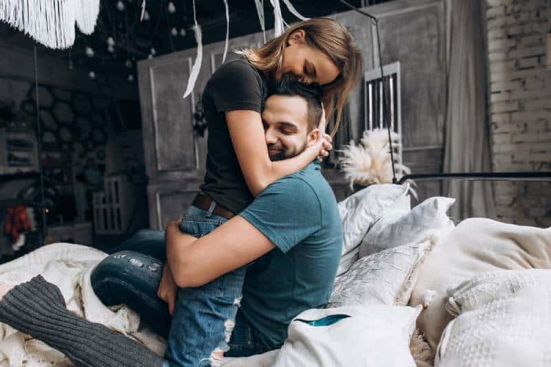 Un couple d'amoureux s'embrasse sur le lit, dans la grande chambre.