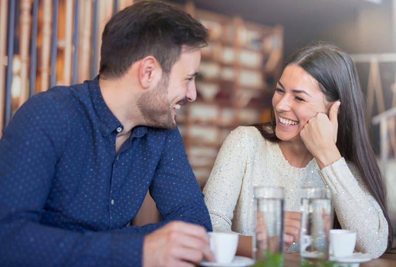 Un couple souriant prend un café au café