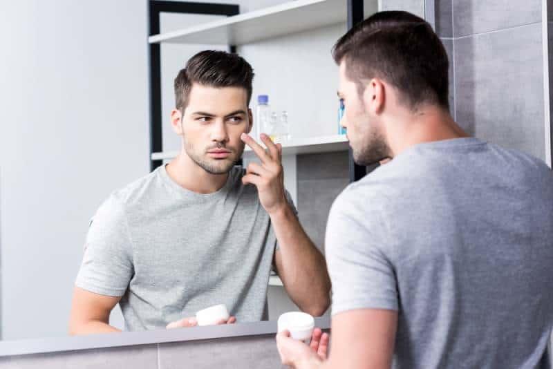 Un homme applique une crème pour le visage dans la salle de bain tout en se regardant dans un miroir