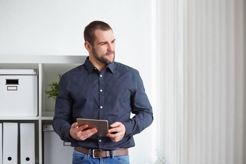 Un homme d'affaires au bureau avec une tablette informatique
