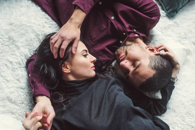 Un homme et une femme s'embrassent dans leur lit