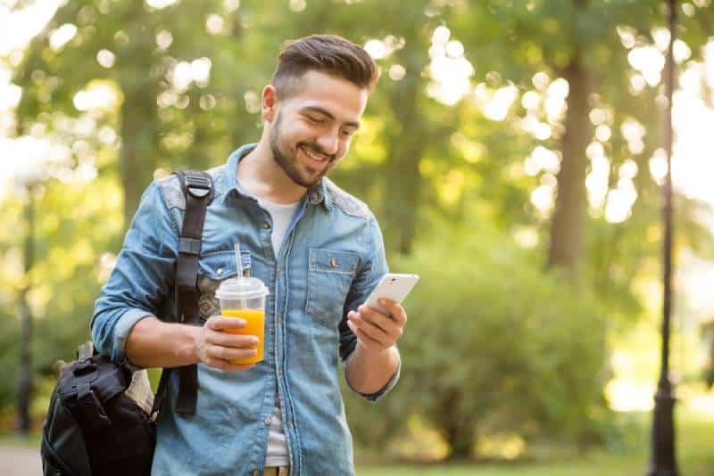 Un homme heureux se promène dans un parc d'automne et sourit