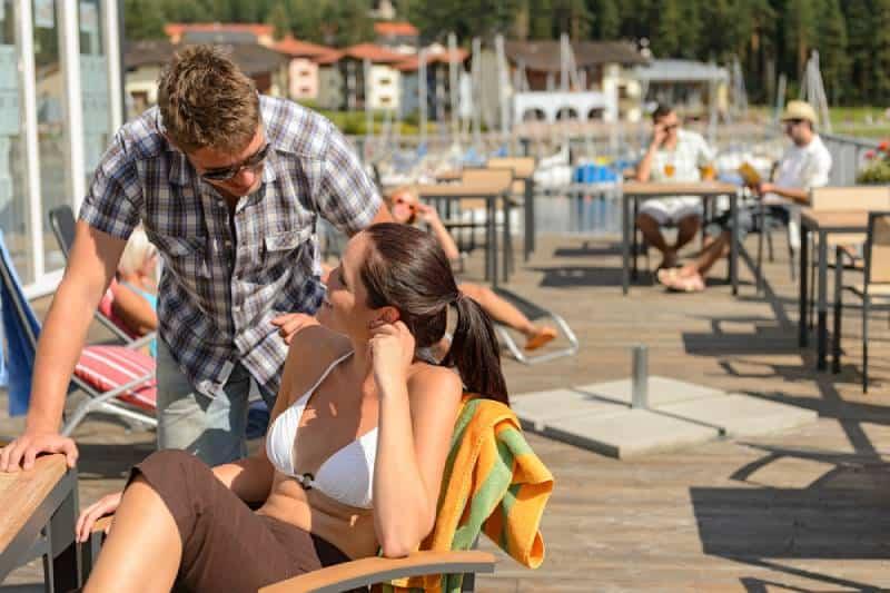 Un homme parle à une femme dehors au bar du lac