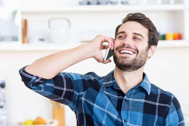 Un homme parle au téléphone et sourit au travail