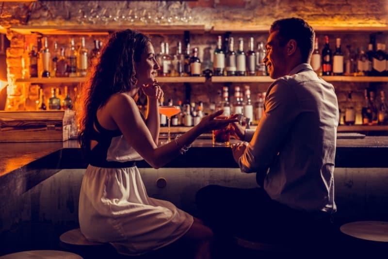 Un jeune couple charmant se détend en s'asseyant au bar