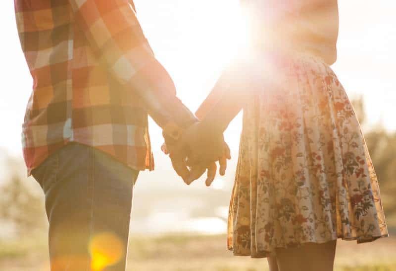 Un jeune couple d'amoureux se promène dans le regardant le coucher de soleil