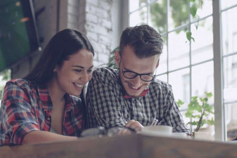 Un jeune couple souriant à l'intérieur