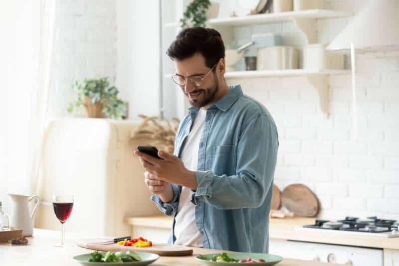 Un jeune homme heureux prépare un dîner romantique
