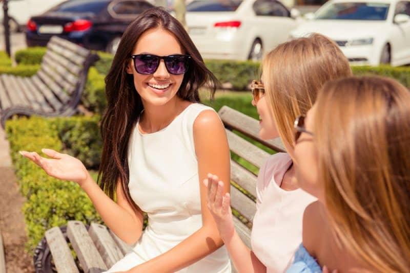 Une femme joyeuse parle à ses amis sur un banc dans un parc