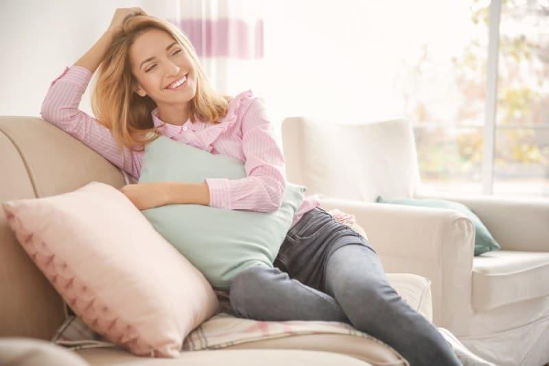 Une femme souriante avec un oreiller moelleux à la maison