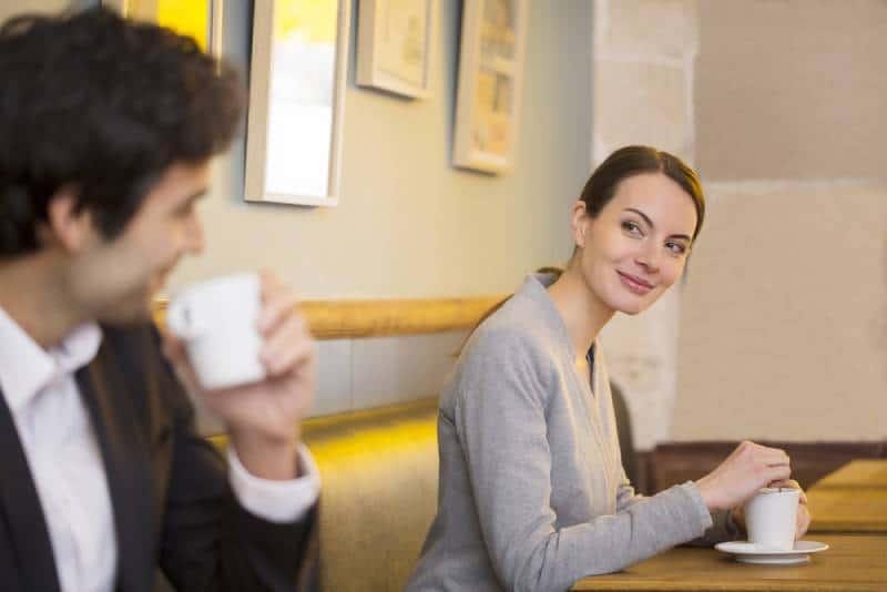 Une femme souriante regarde un homme dans un café