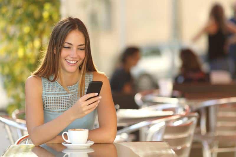 Une fille souriante envoie des SMS sur son smartphone au café