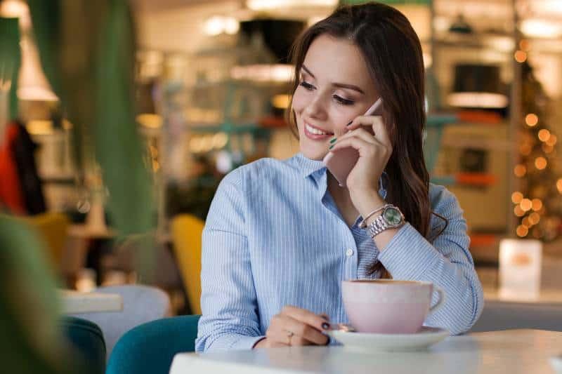 Une fille souriante parle au téléphone dans un café