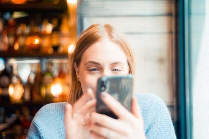 Une fille souriante qui regarde son téléphone