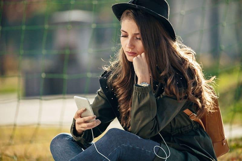 femme inquiète regardant téléphone mobile