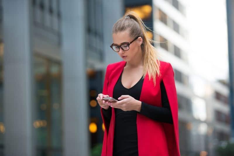 belle femme tenue dactylographier le message sur le téléphone à l'extérieur