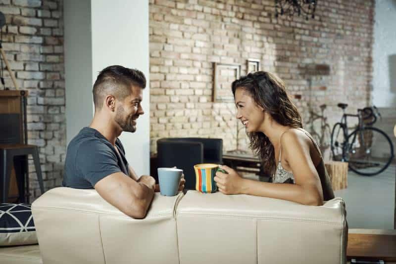 couple assis dans le salon et discutant avec un café