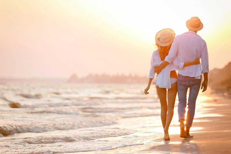 couple avec chapeau marchant sur la plage
