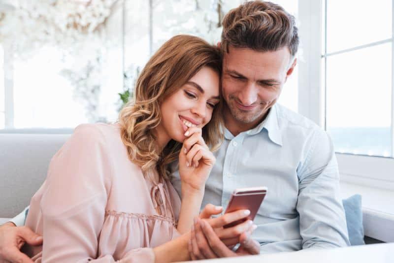 couple dans l'amour s'asseyant et regardant le téléphone dans le bar de café