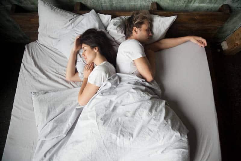 couple dormant sur le lit, dos à dos dans la chambre