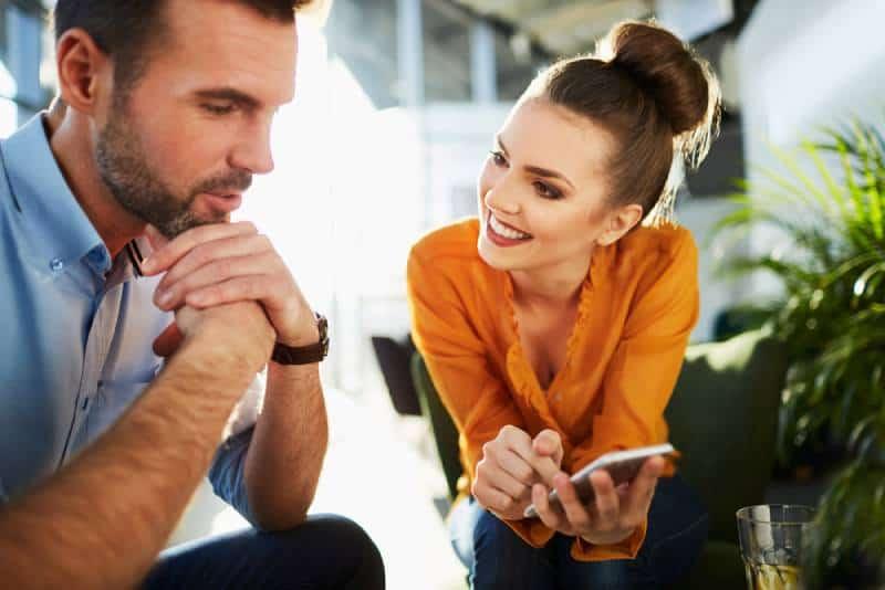 couple heureux assis au café-bar et regardant le téléphone
