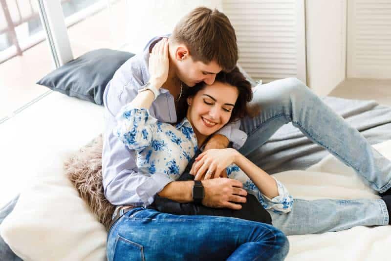 couple heureux assis sur un canapé à la maison