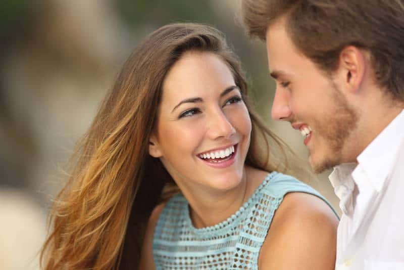 couple riant avec un sourire et se regardant à l'extérieur