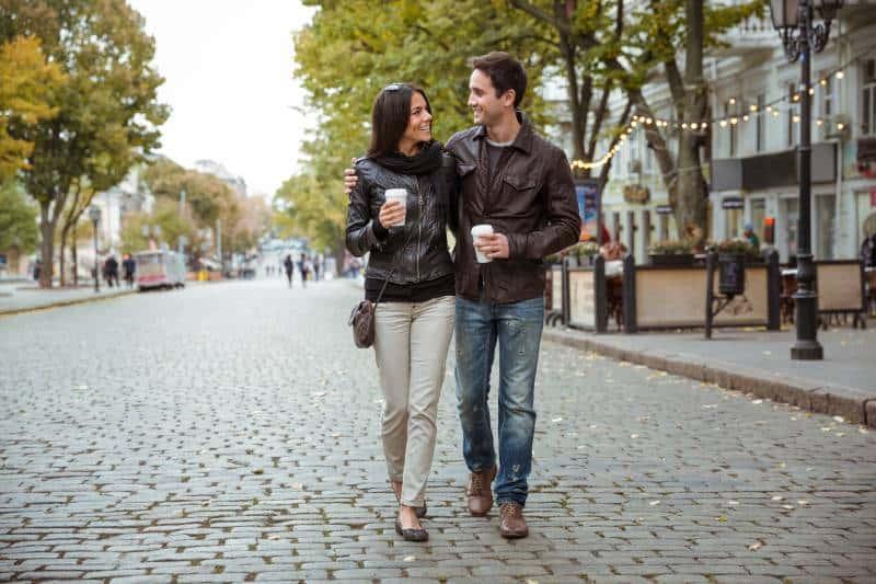 couples étreignant marchant avec un café