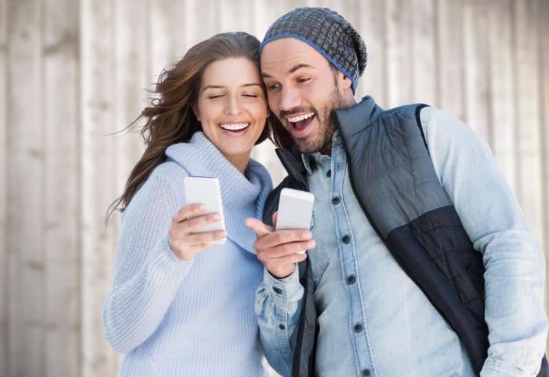 couples heureux à l'extérieur regardant le téléphone